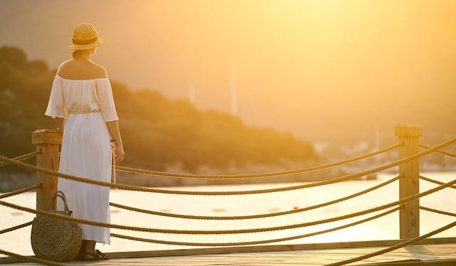 夕日の中佇む夏服の女性